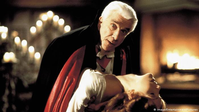 Film still 'Dracula: Dead and Loving It' man holds a woman in his arms, about to bite her neck but looks into camera (Foto: imago/EntertainmentPictures)