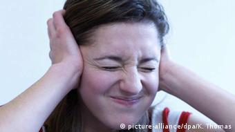 Junge Frau mit schmerzverzerrtem Gesicht haelt sich die Ohren zu (picture-alliance/dpa/K. Thomas)