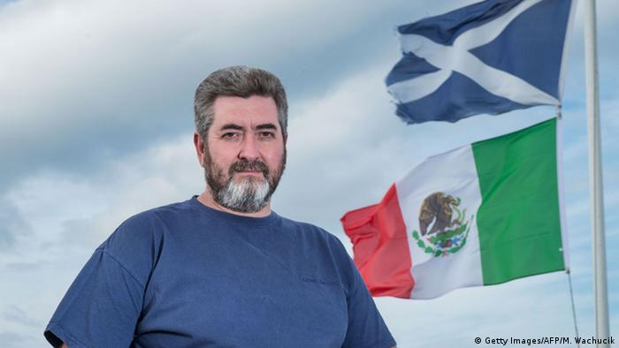 David Milne poses for a photograph beside the Mexican flag and The Saltire, the flag of Scotland on the top of his house, located around 400 metres away from the Donald Trump's International Golf Links course, north of Aberdeen