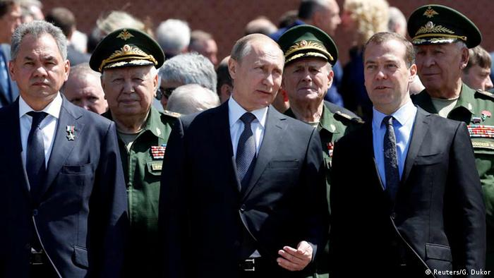Defense Minister Sergei Shoigu, President Vladimir Putin and Prime Minister Dmitry Medvedev attend a wreath-laying ceremony by the Kremlin walls in Moscow