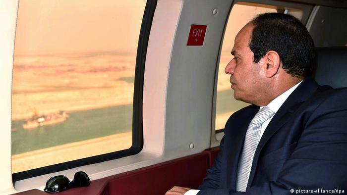 A handout picture provided by the Office of the Egyptian Presidency shows the Egyptian President, Abdel Fattah al-Sisi, gazing out of a window at the new extension to the Suez Canal, Egypt