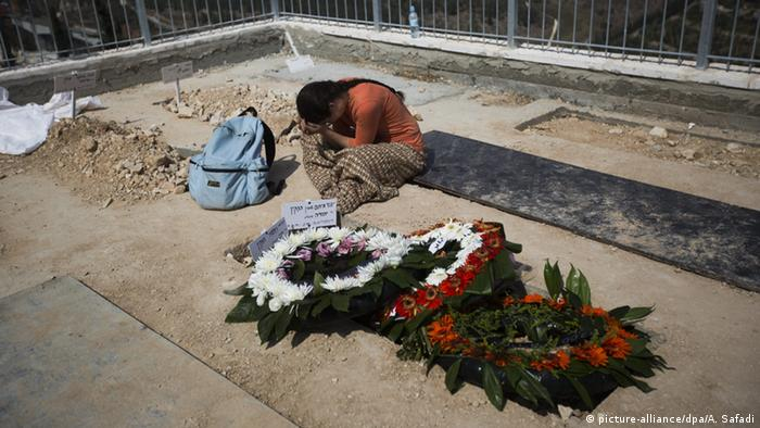 An Israeli woman mourns at the grave of Israeli couple, Eitam and Naama Henkin, at the Mount Herzl cemetery in Jerusalem
