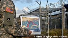 08.04.2014***This photo made during an escorted visit and reviewed by the US military, shows a US Army officer showing a photograph of then operational and now abandoned Camp X-Ray detention facility at the US Naval Station in Guantanamo Bay, Cuba, April 9, 2014. AFP PHOTO/MLADEN ANTONOV (Photo credit should read MLADEN ANTONOV/AFP/Getty Images) Copyright: Getty Images/AFP/M. Antonov