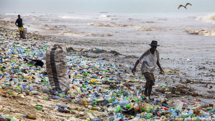 A man collecting waste on the beach: many plastic bottles lying around
