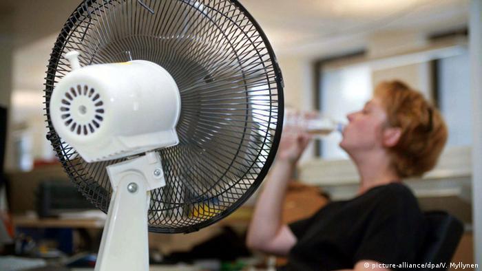 Женщина в офисе пьет воду