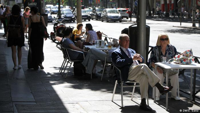 People sit on a café terrace in Madrid