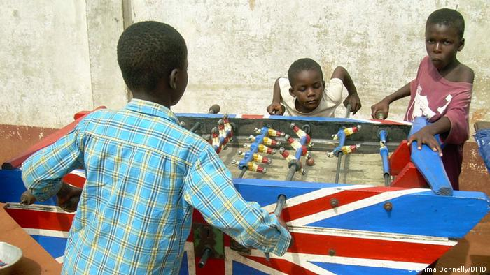 A group of three boys playing table soccer