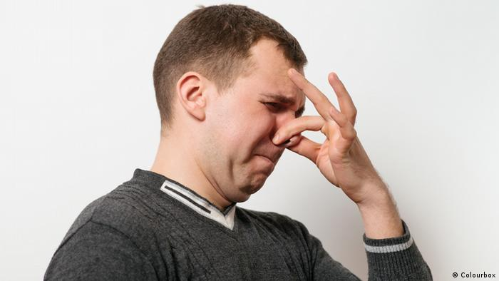 Man holding his nose, Copyright: Colourbox