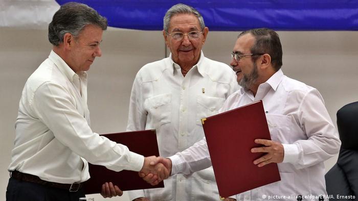 Sob o olhar do presidente cubano Raul Castro, o presidente colombiano Juan Manuel Santos e o líder das FARC Rodrigo Londono apertam as mãos em Havana.