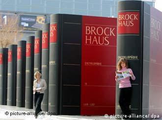 Exhibition of huge Brockhaus books with women weaving inbetween