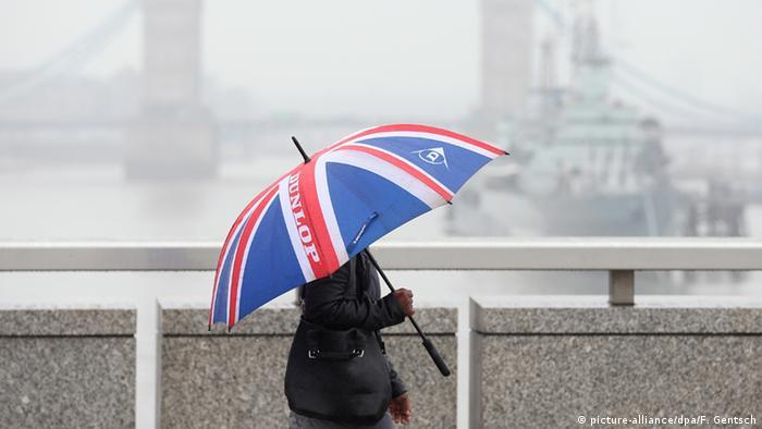 Großbritannien London Frau geht mit Union Jack Regenschirm über die Tower Bridge