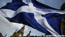 11.05.2015 A member of public flies a giant Scottish Saltire flag outside the Houses of Parliament shortly before Scotland first minister Nicola Sturgeon posed with newly-elected Scottish National Party (SNP) MPs during a photocall in London on May 11, 2015. The SNP won a landslide in Scotland in the May 7 general election, destroying the Labour party north of the border in a historic leap forward which could increase pressure for a fresh referendum on independence. The nationalists won 56 of 59 parliamentary seats in Scotland up from just six at the last vote in 2010. AFP PHOTO / ADRIAN DENNIS (Photo credit should read ADRIAN DENNIS/AFP/Getty Images) Copyright: Getty Images/AFP/A. Dennis