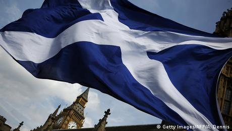 A member of public flies a giant Scottish Saltire flag outside the Houses of Parliament in London