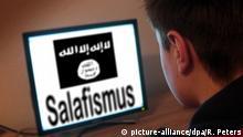 Symbolbild zu den Anwerbeversuchen der radikal-islamistischen IS Islamischer Staat bei minderjährigen Jugendlichen Jugendlicher sitzt am Bildschirm eines PC s mit Flagge des IS und Schriftzug Salafis | Verwendung weltweit © picture-alliance/dpa/R. Peters