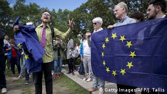 Demonstrators hold EU flags as they protest against the outcome of the UK's EU referendum.