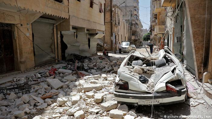 A damaged vehicle is seen on the debris of buildings after a warcraft belonging to the Russian army carried out an attack in Aleppo, Syria
