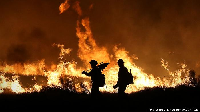 Two firefighters are in silhouette as they walk at night in front of flames from a California wildfire.