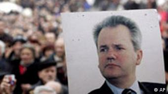 A socialist party supporter holds a photo of Slobodan Milosevic