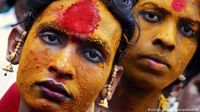 Hijras with colored powder on their face in the Indian village of Koovagam