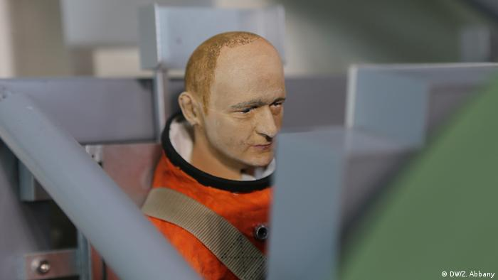 A model man sits in a model Orion spacecraft