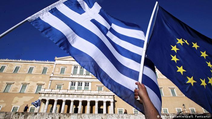 People wave Greek and EU flags outside the Greek parliament in Athens
