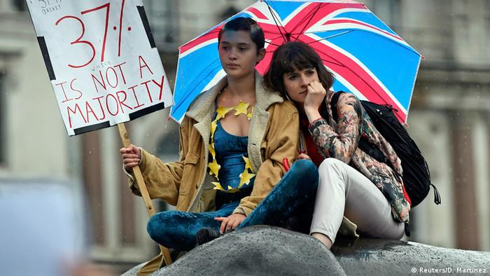 Two girls on a statue as Brexit opponents