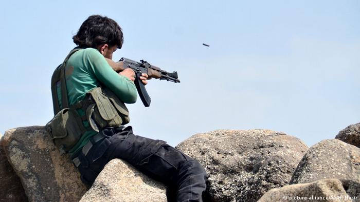 A Syrian rebel fires an assault rifle at Islamic State targets