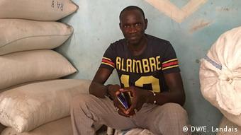 Mantany Dieye sitting by some sacks in his shop in Dakar © DW/E. Landais