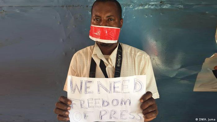 A Tanzanian journalist holding a protest sign.