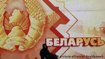 Женщина с коляской на фоне огромного плаката с белорусским гербом