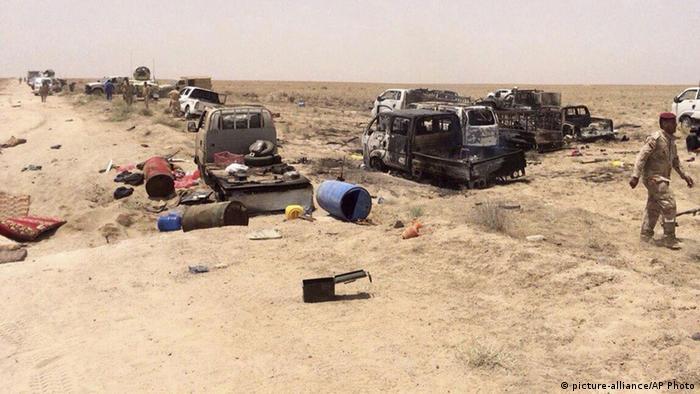 Сгоревшие машины и разбросанные предметы после авианалета на позиции ИГ