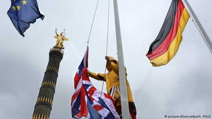 A man takes down the British flag in Berlin