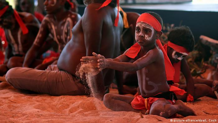 A young aboriginal dancer plays in the sand during the Kenbi Native land claim ceremony in Australia
