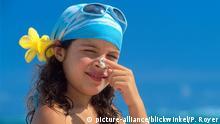 Mädchen am Strand, trägt Kopftuch, Sonnenbrille, Blume im Haar, cremt sich die Nase. +++ (C) picture-alliance/blickwinkel/P. Royer