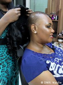 Female hairdresser puts on a wig on the head of a female client.