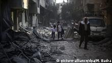 FILE - Syrian boys hold hands as they walk amid the rubble of buildings destroyed following an airstrike which according to local reports was conducted by forces loyal to the Syrian Government on the rebel-held area of Douma, outskirts of Damascus, Syria, 21 October 2015. The rebel held territory on the outskirts of Damascus has been one of the most targeted by regime airstrikes, which includes the use of barrel bombs, resulting in the deaths of hundreds of civilians, leaving thousands injured and the town in ruins. EPA/MOHAMMED BADRA (Zu dpa Zivile Opfer im syrischen Bürgerkrieg) +++(c) dpa - Bildfunk+++ | Copyright: picture-alliance/dpa/M. Badra
