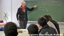 ARCHIV - Einen Deutschkurs für Flüchtlinge führt Carmen Hahn am 08.02.2016 in der Gemeinschaftsunterkunft in Güstrow (Mecklenburg-Vorpommern) durch. Sie ist eine von drei ehrenamtlichen Lehrkräften, die den Asylbewerbern in der Gemeinschaftsunterkunft beim Erlernen der deutschen Sprache helfen. Foto: Bernd Wüstneck/dpa +++(c) dpa - Bildfunk+++ | Verwendung weltweit (c) picture-alliance/dpa/B. Wüstneck