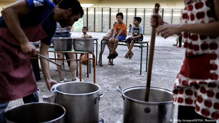 Volunteers cooking in the courtyard of an abandoned school used by volunteers for hosting refugees in Athens. (Foto: ARIS MESSINIS/AFP/Getty )