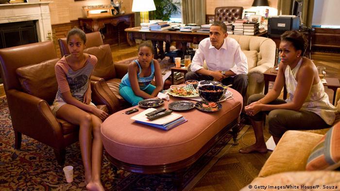 US-Präsident Barack Obama sitzt mit seiner Ehefrau Michele und seinen beiden Töchtern zusammen vor dem Fernseher mit einer Pizza. (Foto: picture alliance/dpa/Pete Souza)