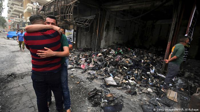Iraqi men hug at the site of a truck bomb that killed 292 people in Baghdad over the weekend