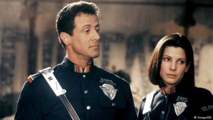 Sylvester Stallone und Sandra Bullock in Uniformen. Filmstill aus Demolitian Man.