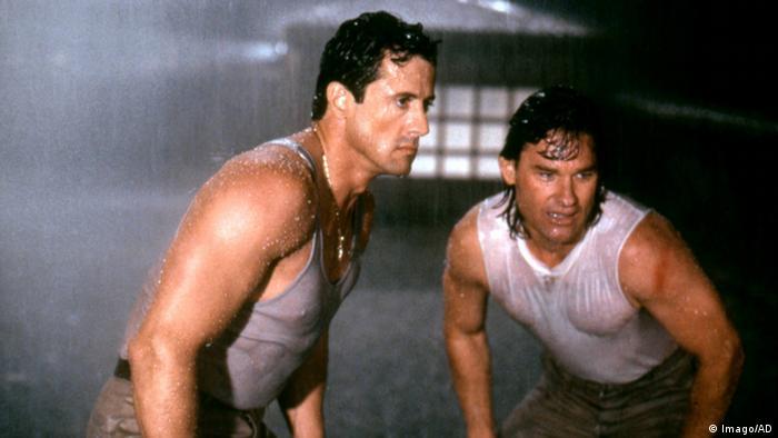 Sylvester Stallone und Kurt Russell stehen im strömenden Regen.