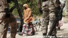 ARCHIV 2015 **** In this photo taken Wednesday, April 8, 2015, a woman walks past Nigerian Soldiers at a checkpoint in Gwoza, Nigeria, a town newly liberated from Boko Haram. Each day brings new reports of atrocities, with mass graves being discovered in towns seized back from the militants who had set up a so-called ¿Islamic caliphate¿ across a great swath of northeast Nigeria. Boko Haram's nearly 6-year-old Islamic uprising in northeast Nigeria that has killed thousands ¿ a reported 10,000 just last year ¿ and forced more than 1.5 million from their homes. (AP Photo/Lekan Oyekanmi) | © picture-alliance/AP Photo/L. Oyekanmi