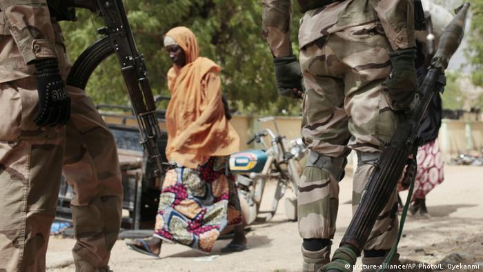 A woman walks past Nigerian soldiers at a checkpoint