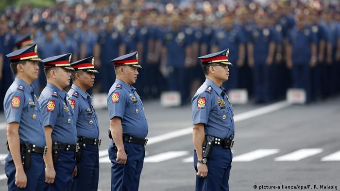 Filipino policemen stand during a flag raising ceremony inside Camp Crame in Quezon City, east of Manila, Philippines