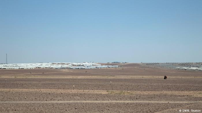 Refugees who live in Azraq Camp walk between residential areas and the supermarket