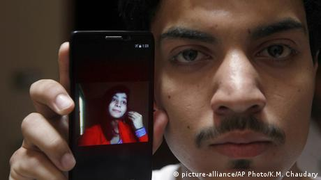 Man holds phone with photo of a young woman on the screen