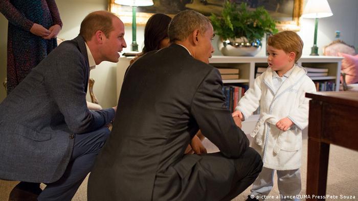 US-Präsident Barack Obama schüttelt dem kleinen Prinz George die Hände. Sein Vater Prinz William und Kate hocken neben ihm. (Foto: picture alliance/dpa/Pete Souza)