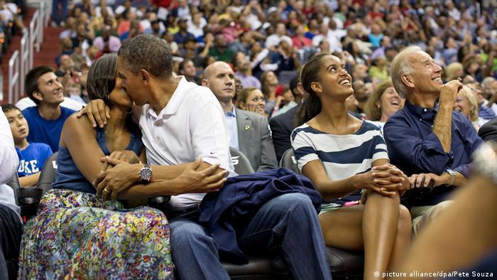 US-Präsident Barack Obama umarmt seine Frau Michele und küsst sie leidenschaftlich während eines Baseballspiels. (Foto: picture alliance/dpa/Pete Souza)