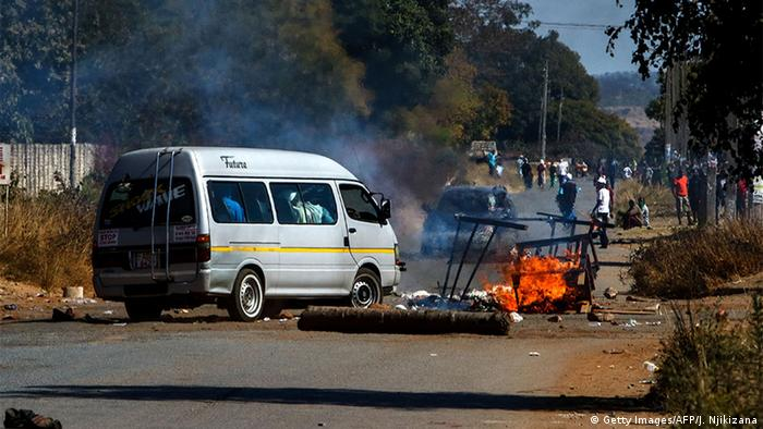 Minibus in Harare drives past a tyre burning in the street